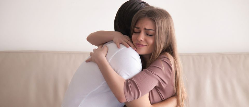 Portrait of emotional young couple hugging each other tightly, boyfriend and girlfriend embracing sitting on couch, reconciliation after argument, love you so much, strong affection in relationships Shutterstock/ Fizkes   NYC Gov't Says A Hug Is Sexual Harassment