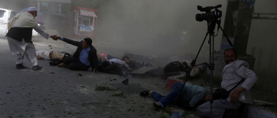 Afghan journalists are seen after a second blast in Kabul