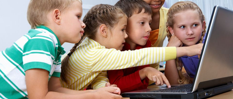 Girls and boys at school look at a computer. [Shutterstock - Pressmaster]