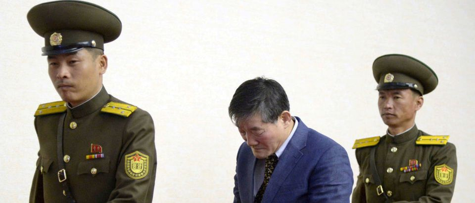 A man (C) who identified himself as Kim Dong Chul, previously said he was a naturalised American citizen and was arrested in North Korea in October, leaves after a news conference in Pyongyang, North Korea, in this photo released by Kyodo March 25, 2016. REUTERS/Kyodo/File Photo