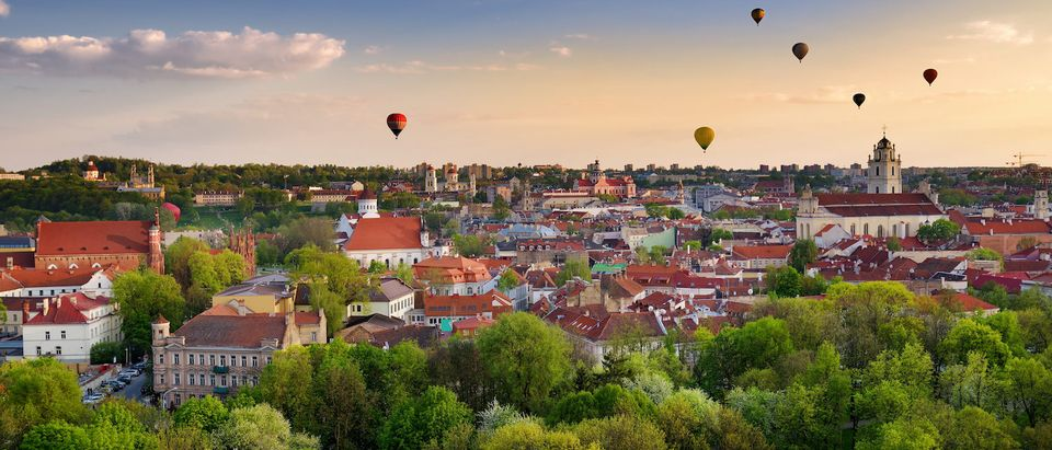 Beautiful summer panorama of Vilnius old town with colorful hot air balloons in the sky, taken from the Gediminas hill. (Shutterstock/MNStudio) | Watchdog Cancels Meeting For Dem Travel