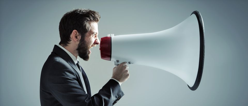 Young businessman with a megaphone. Shutterstock