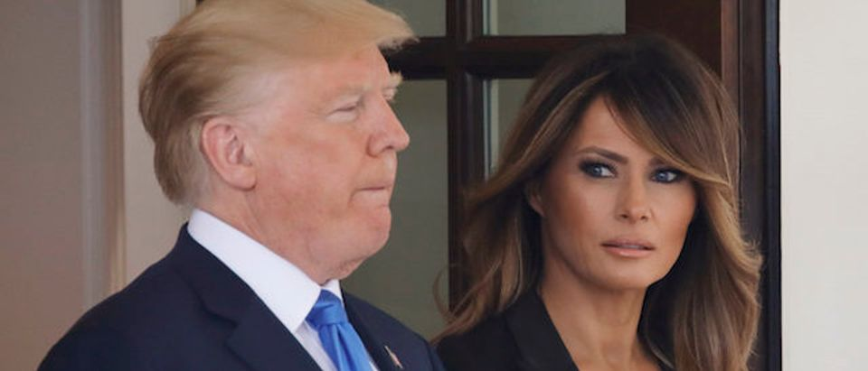 First lady Melania Trump looks over at U.S. President Trump as they wait to welcome French President Macron at the White House in Washington