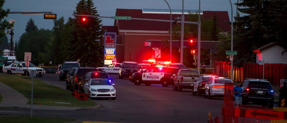 Police officers block off roads after a shooting incident in southwest Edmonton