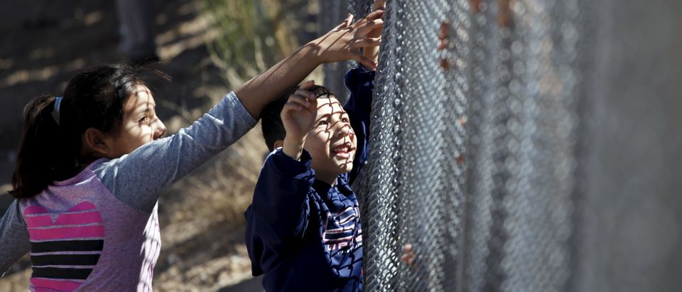 Children touch the hands of a family member through the border fence between Ciudad Juarez and El Paso, United States, after a bi-national Mass in support of migrants in Ciudad Juarez