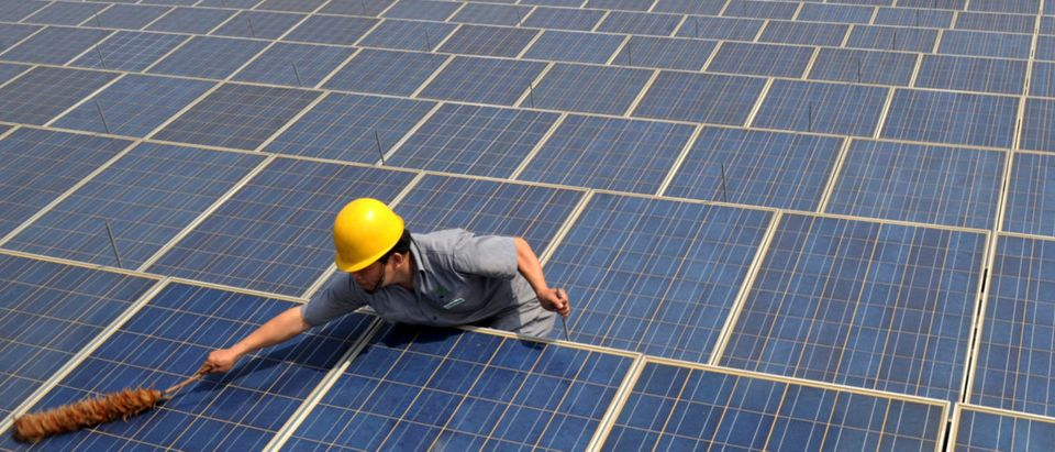 A worker cleans solar panels on the rooftop of the Yiwu International Trade City in Yiwu