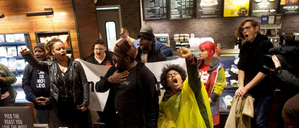 Protesters demonstrate inside a Center City Starbucks, where two black men were arrested, in Philadelphia