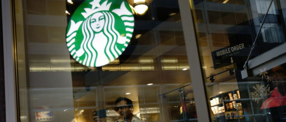 Protesters marching down Market Street are seen reflected in a Starbucks storefront in Philadelphia