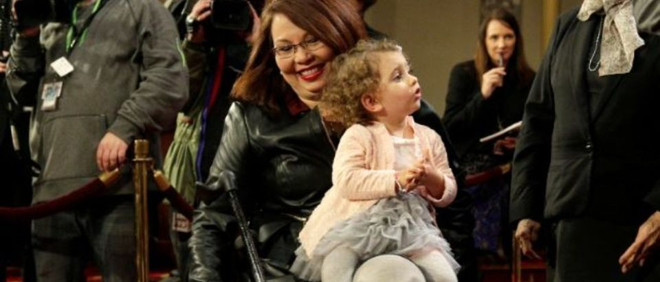 Senator Tammy Duckworth (D-IL) carries her daughter Abigail during a mock swearing in with U.S. Vice President Joe Biden during the opening day of the 115th Congress on Capitol Hill in Washington, U.S., January 3, 2017. REUTERS/Joshua Roberts   Duckworth Asks For Rules Change For Baby