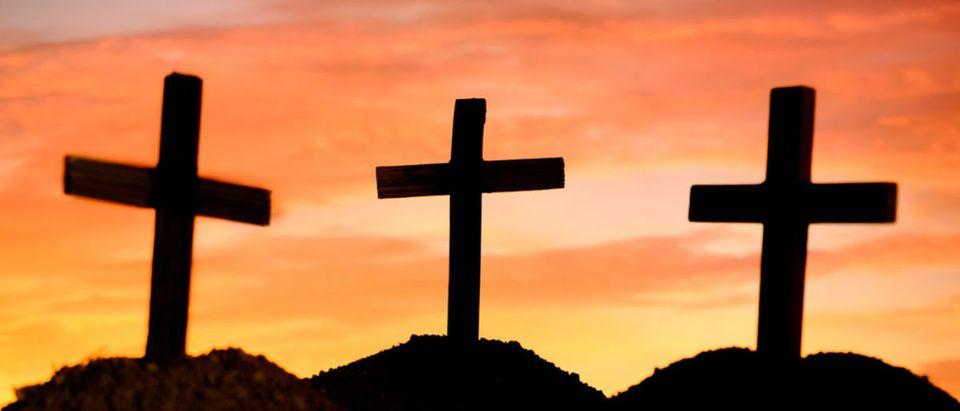 Three crosses stand on a hill. (Shutterstock/Doidam 10)