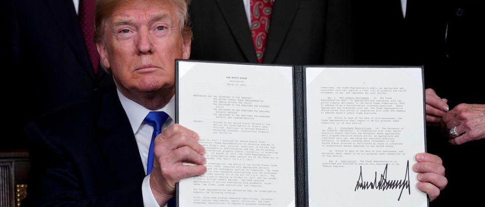 U.S. President Donald Trump holds his signed memorandum on intellectual property tariffs on high-tech goods from China, at the White House in Washington, U.S. March 22, 2018. REUTERS/Jonathan Ernst