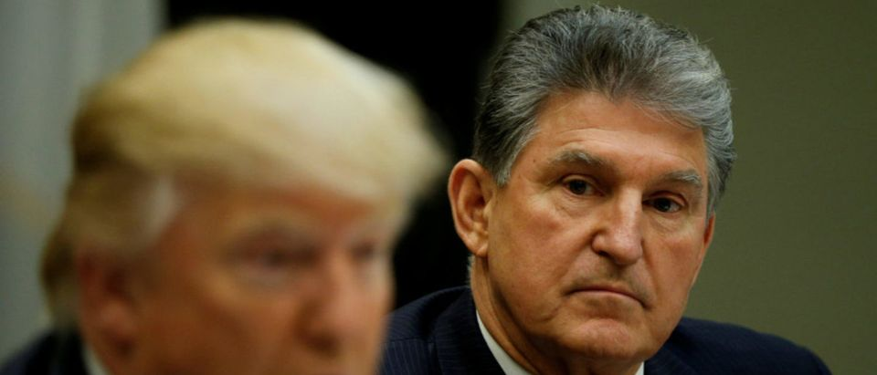 FILE PHOTO: West Virginia Democrat Sen. Joe Manchin (R), who broke ranks to vote with Republicans for Jeff Sessions to become U.S. Attorney General, looks towards U.S President Donald Trump during a Supreme Court listening session at the White House in Washington, DC, U.S., February 9, 2017. REUTERS/Kevin Lamarque/File Photo