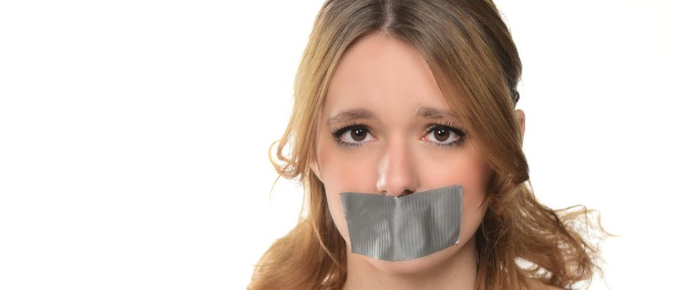 Pictured is a scared young woman with tape over her mouth. (Shutterstock/KlaraBstock)