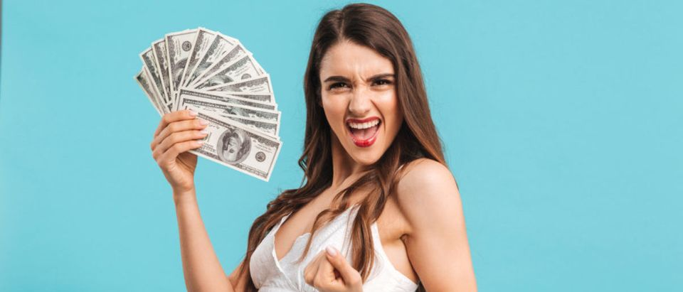 Portrait of a cheerful young girl in summer dress showing money banknotes and celebrating isolated over blue background (Shutterstock/Dean Drobot)