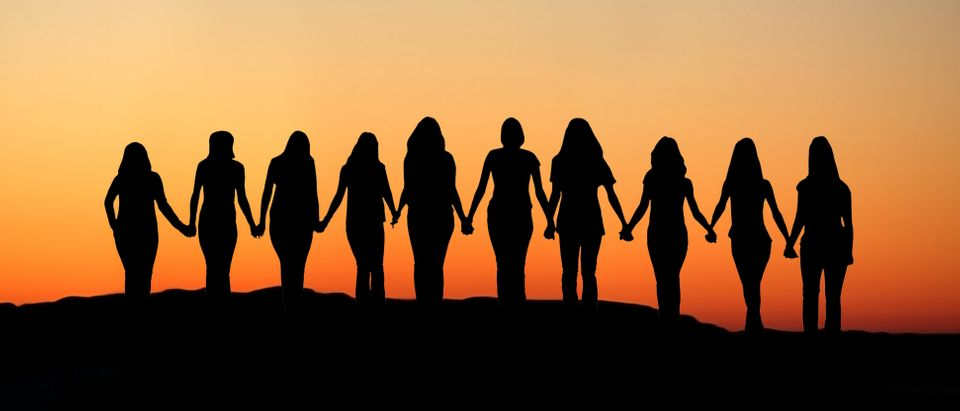 Sunrise silhouette of 10 young women walking hand in hand. (Shutterstock)