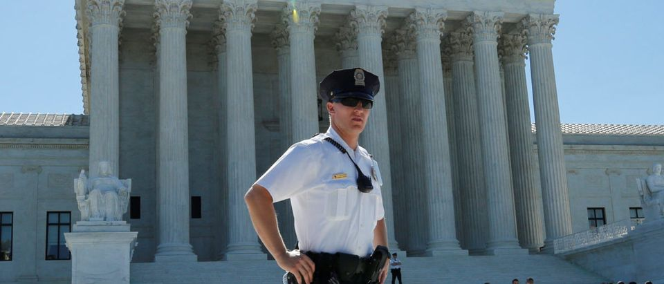 A police officer stands outside the U.S. Supreme Court building after the Court sided with Trinity Lutheran Church, which objected to being denied public money in Missouri, in Washington, U.S., June 26, 2017. REUTERS/Yuri Gripas