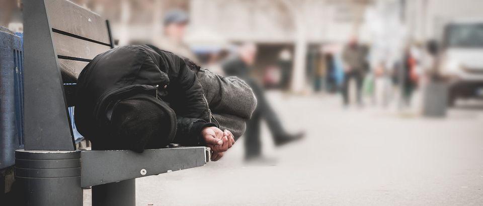 Poor homeless man or refugee sleeping on the wooden bench on the urban street in the city, social documentary concept, selective focus. (Shutterstock/Srdjan Randjelovic)