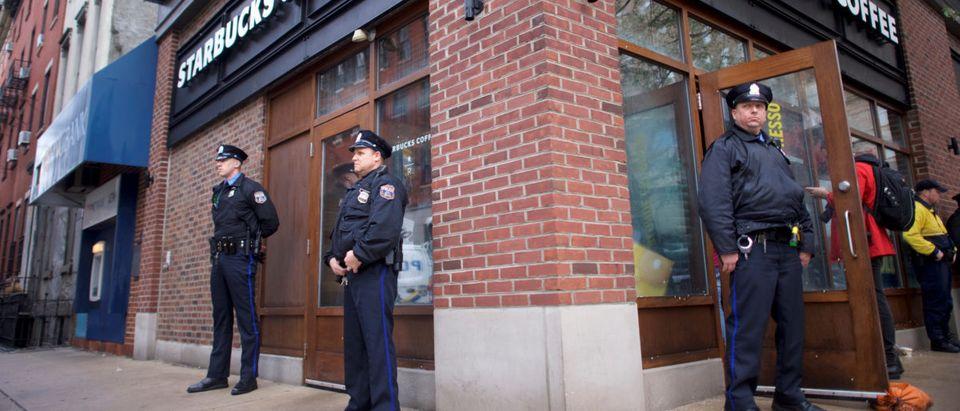 Police officers monitor activity outside as protestors demonstrate inside a Center City Starbucks, where two black men were arrested, in Philadelphia, Pennsylvania U.S., April 16, 2018. REUTERS/Mark Makela