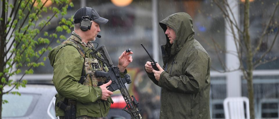 NASHVILLE, TN - APRIL 22: Law enforcement stand outside a Waffle House where four people were killed and two were wounded after a gunman opened fire with an assault weapon on April 22, 2018 in Nashville, Tennessee. Travis Reinking, 29, of Morton, IL, is person of interest in the shooting and is suspected to have left the scene naked. (Photo by Jason Davis/Getty Images)
