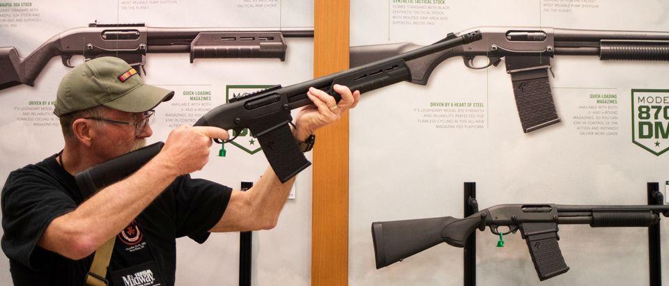A man aims a Remington firearm at the annual NRA meeting in Dallas, Texas