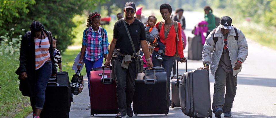 FILE PHOTO: Three families that claimed to be from Burundi walk down Roxham Road to cross into Quebec at the US-Canada border in Champlain New York