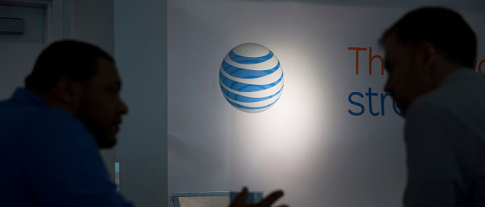 The AT&T Inc. logo is seen past a customer and a retail sales consultant at an AT&T store in Washington, D.C., U.S., on Tuesday, April 21, 2015. AT&T Inc., the second-largest U.S. wireless carrier, is expected to release earnings figures data on April 22. (Photo: Andrew Harrer/Bloomberg via Getty Images)