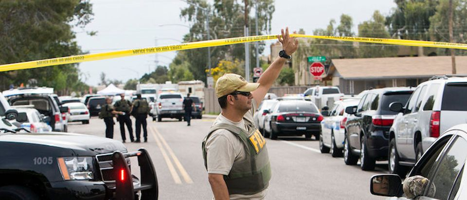 An FBI agent lift police tape at one of the scenes of a multiple location shooting that has injured at least four people in Mesa, Arizona at one of the scenes of a multiple location shooting that has injured at least four people in Mesa, Arizona