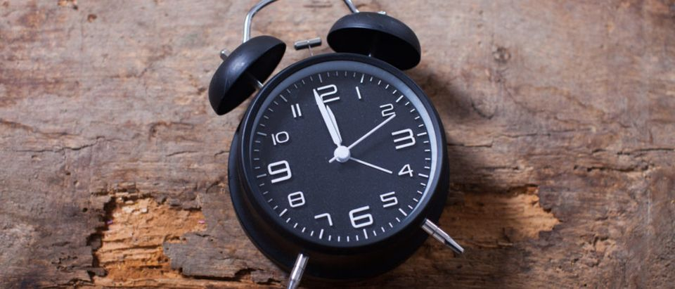 An analog clock sits on a table. (Shutterstock/NIKITA TV)