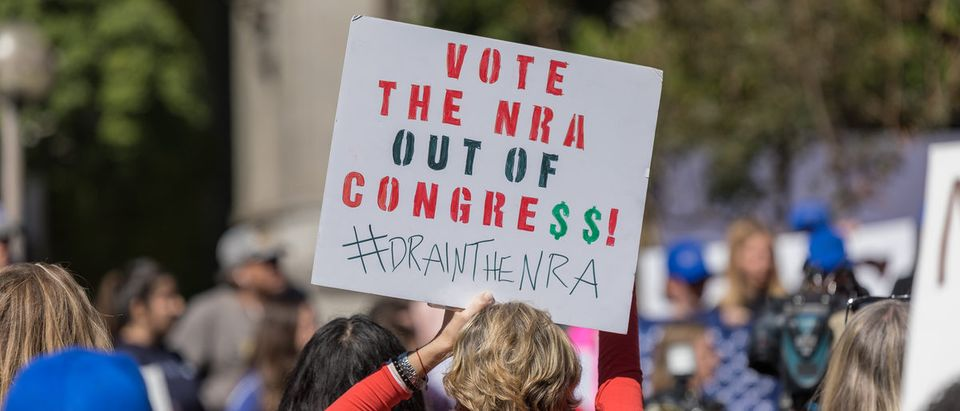 """Vote the NRA out of Congress!"" sign held by a protester at the People's Rally Against Gun Violence in Los Angeles, Calif., Feb. 19, 2018. (Shutterstock/Karl_Sonnenberg) 