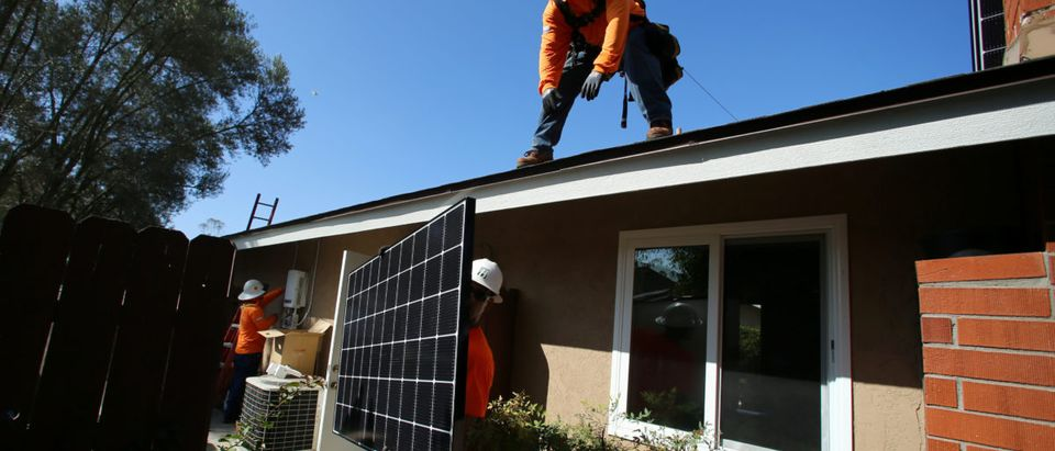 Workers lift a solar panel onto a roof during a residential solar installation in Scripps Ranch, San Diego, California, U.S. October 14, 2016. Picture taken October 14, 2016. REUTERS/Mike Blake