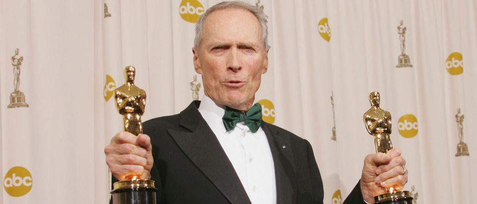 """Producer Clint Eastwood poses with his awards for Best Motion Picture and Best Director for """"Million Dollar Baby"""" backstage during the 77th Annual Academy Awards on February 27, 2005 at the Kodak Theater in Hollywood, California. (Photo by Carlo Allegri/Getty Images)"""