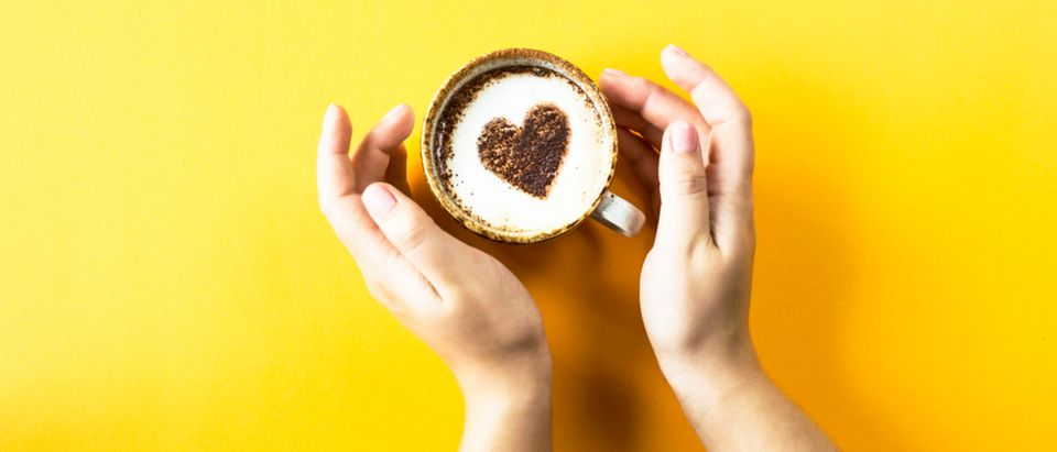 A female hand holds a cup of coffee on which a heart is drawn. Laik in social networks concept. Top view, flat lay Shutterstock/ VSamarkina | Caffeine Addicts: Top Four Coffee Shops
