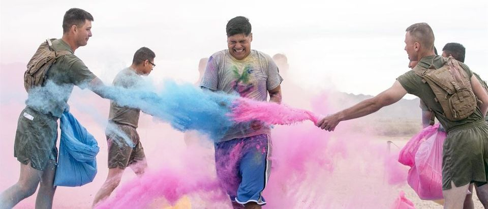 Marines throw colored powder onto participants of the annual Colorful Consent 5k Run to mark Sexual Assault Awareness and Prevention Month at Marine Corps Air Ground Combat Center Twentynine Palms, Calif., April 7, 2017. Marine Corps Photo by Cpl. Julio McGraw