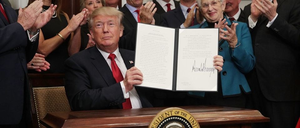 """WASHINGTON, DC - OCTOBER 12: U.S. President Donald Trump shows an executive order after he signed it as Sen. Rand Paul (R-KY), Vice President Mike Pence, Rep. Virginia Foxx (R-NC) and Secretary of Labor Alexander Acosta look on during an event in the Roosevelt Room of the White House October 12, 2017 in Washington, DC. President Trump signed the executive order to loosen restrictions on Affordable Care Act """"to promote healthcare choice and competition."""" (Photo by Alex Wong/Getty Images)"""