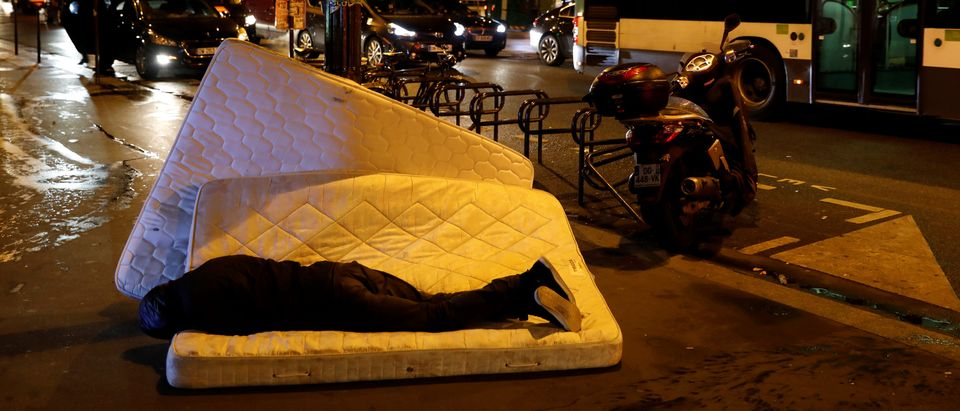 A man sleeps on a mattress next to the SCMR (Drug supervised injection site), the first supervised injection room for drug users, in Paris, October 17, 2016. REUTERS/Benoit Tessier