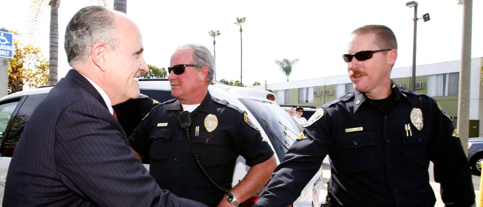 Former New York Mayor Rudy Giuliani shakes hands with police officers during visit to San Diego