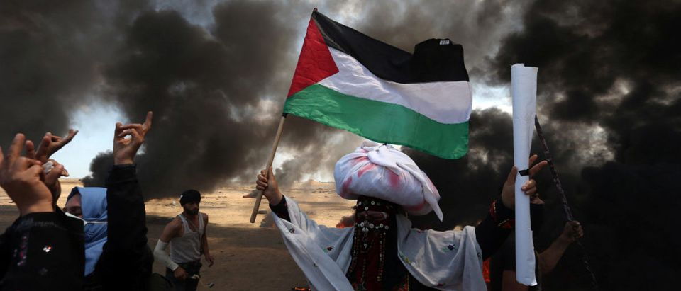 Female demonstrator holds a Palestinian flag during a protest against U.S. embassy move to Jerusalem and ahead of the 70th anniversary of Nakba, at the Israel-Gaza border in the southern Gaza Strip