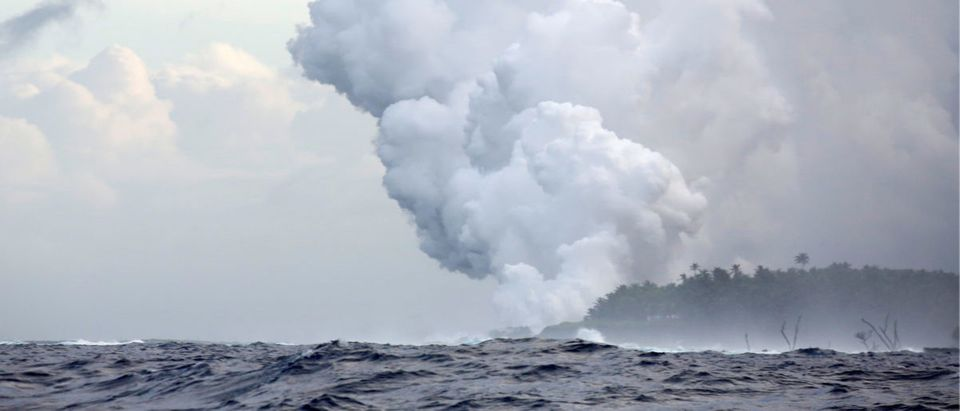 Steam and volcanic gases rise as lava flows into the Pacific Ocean southeast of Pahoa