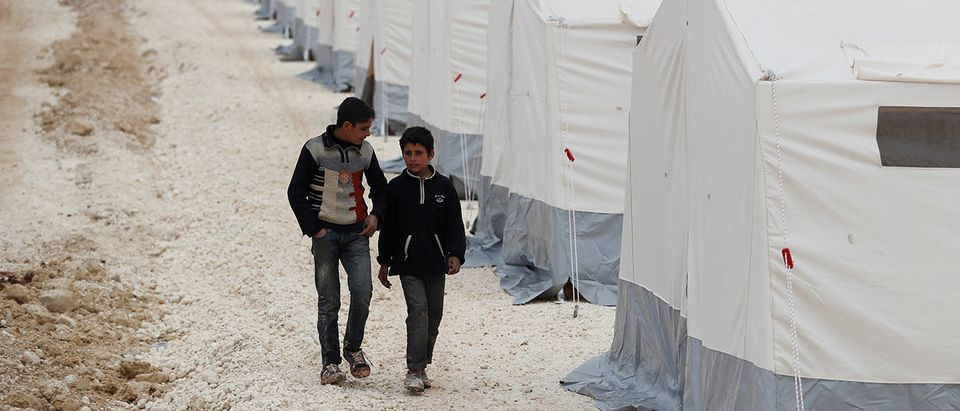 Displaced Syrian boys walk past by tents supplied by Turkish Red Crescent at Kelbit camp, near the Syrian-Turkish border, in Idlib province