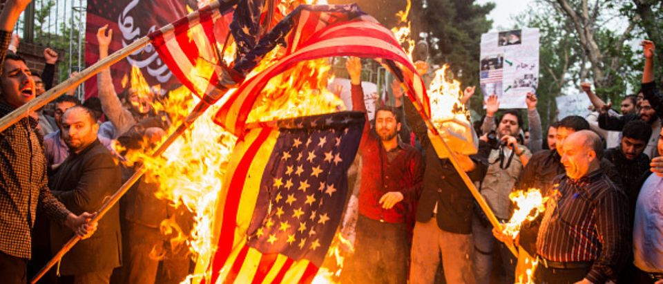 Iranians burn American flags during an anti-U.S. demonstration outside the former U.S. embassy headquarters in Tehran, Iran, on Wednesday, May 9, 2018. (Photo: Ali Mohammadi/Bloomberg via Getty Images) | Reporters Fawn Over Iran Ayatollah