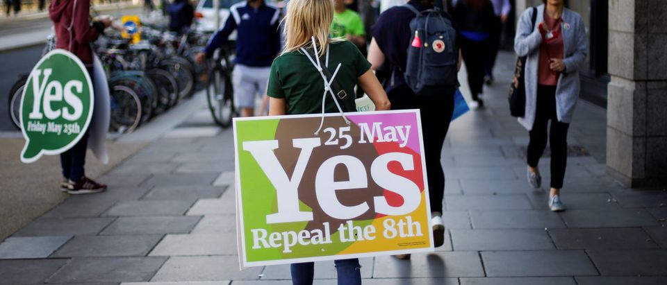A woman carries a placard as Ireland holds a referendum on liberalising abortion laws, in Dublin, Ireland, May 25, 2018. REUTERS/Max Rossi