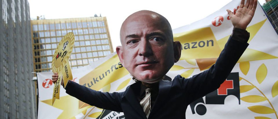 BERLIN, GERMANY - APRIL 24: An activist dressed as Amazon CEO Jeff Bezos joins a protest gathering outside the Axel Springer building on April 24, 2018 in Berlin, Germany. Several hundred Amazon warehouse workers from Germany, Poland and Italy protested outside the Axel Springer building, where inside Bezos was scheduled to receive an award for innovation. The workers claim Amazon pays too little and offers too few benefits. (Photo by Sean Gallup/Getty Images)