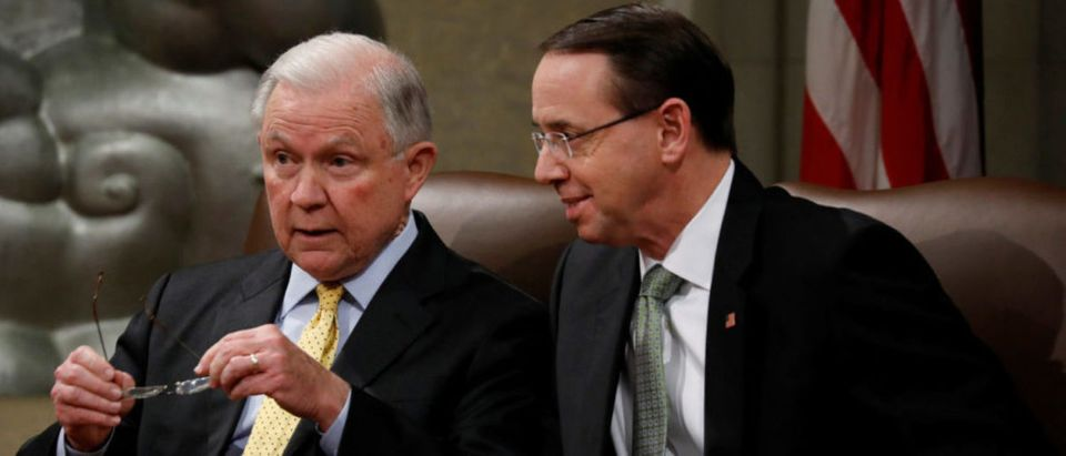 Deputy Attorney General Rod Rosenstein speaks with U.S. Attorney General Jeff Sessions at a summit about combating human trafficking at the Department of Justice in Washington
