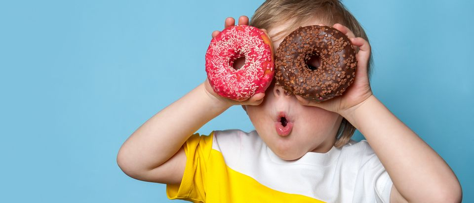 Kid holding donuts