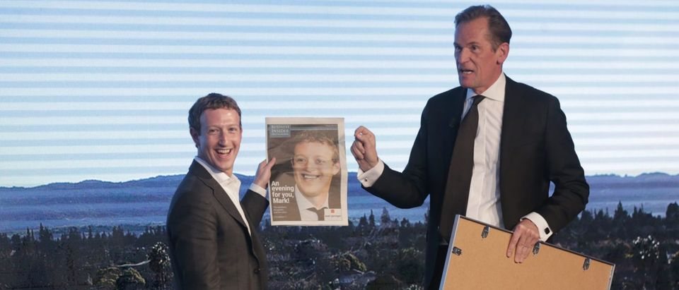 Facebook founder and chief Mark Zuckerberg (L) receives a newspaper from Springer CEO Mathias Doepfner during the Axel Springer Award in Berlin on February 25, 2016. Facebook announced it was donating computer servers to a number of research institutions across Europe, starting with Germany, to accelerate research efforts in artificial intelligence (AI) and machine learning. (Photo: KAY NIETFELD/AFP/Getty Images) | Zuckerberg Rejects Calls To Pay Media