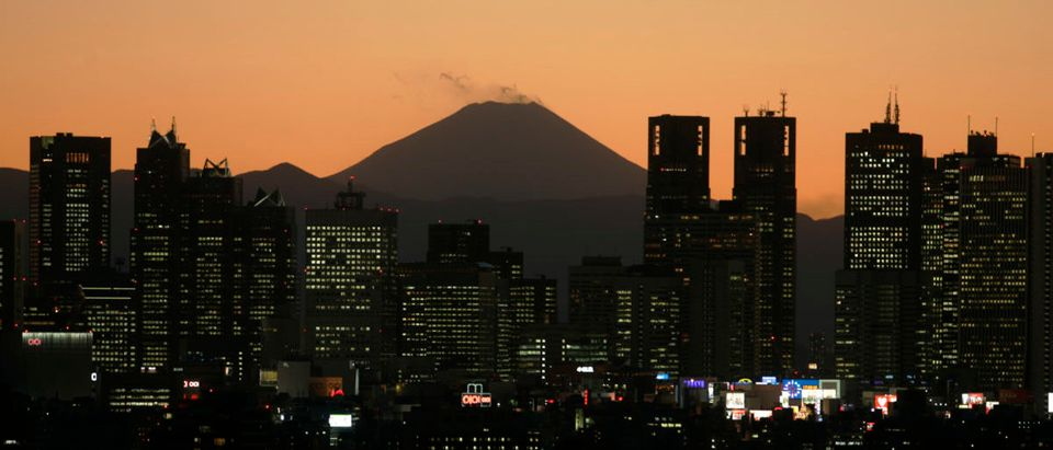 A night view shows Japan's Mt. Fuji seen beyond high-rise buildings in Tokyo