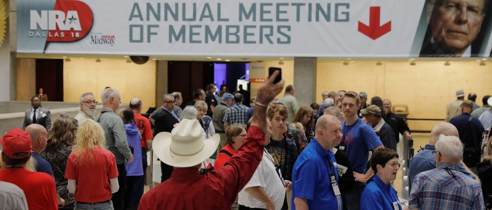 Attendees wait to enter the convention hall where the National Rifle Association (NRA) will hold its annual meeting in Dallas, Texas