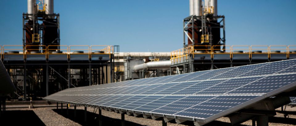 FILE PHOTO: Solar panels are seen in front of a natural gas power plant at the Tahoe-Reno Industrial Center in McCarran
