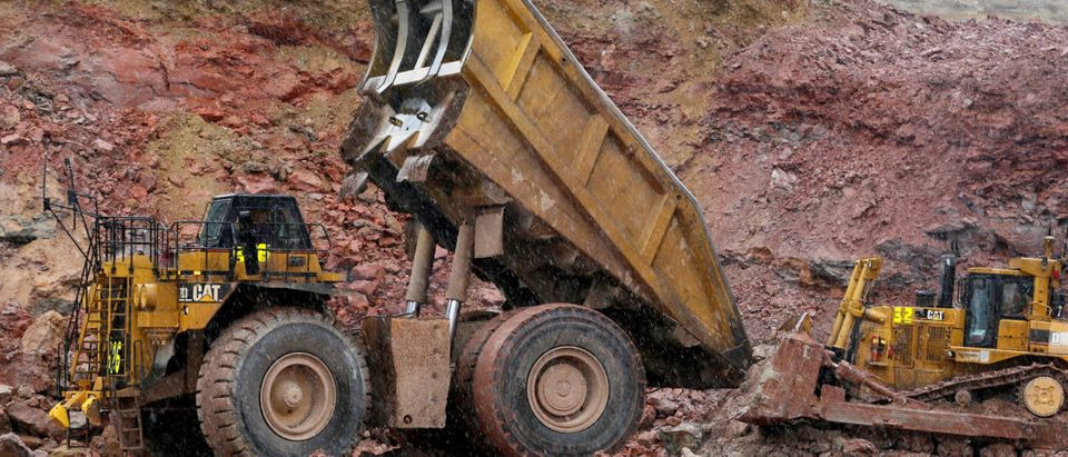FILE PHOTO: A giant Newmont Mining haul truck which is stuck in the mud gets a push from a conventionally sized bulldozer at Newmont's Carlin gold mine operation near Elko,