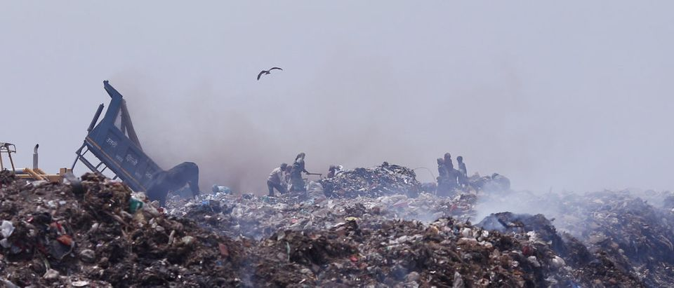 People collect recyclable materials as smoke billows from a burning garbage dump site in New Delhi